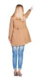 Tillbaka sikt av att peka den bruna kappan för womanin Fotografering för Bildbyråer