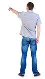 Tillbaka sikt av att peka unga män i skjorta och jeans Arkivbild