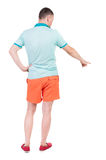 Tillbaka sikt av att peka unga män i t-skjorta och kortslutningar Fotografering för Bildbyråer