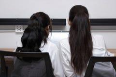 Tillbaka sikt av attraktiv ung asiatisk affärskvinna som två tillsammans använder bärbara datorn i modernt kontor Lagarbetsaffärs royaltyfria foton