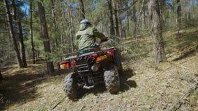 Tillbaka sikt av ATV-ryttaren som fungerar hans av-väg medel och flyttning till och med skogglidningen från sida till sidan extre arkivfilmer