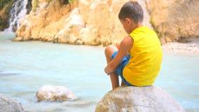 Tillbaka sikt av barnsammanträde på stenen stock video