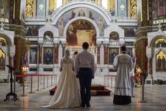 Tillbaka sikt av bruden och brudgummen i kyrka Royaltyfri Bild