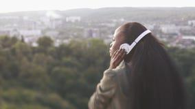 Tillbaka sikt av den attraktiva Afro--amerikan flickan med långt brunt hår som sätter på hörlurar och tycker om stadssikten stock video
