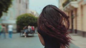 Tillbaka sikt av den attraktiva långhåriga lockiga brunettkvinnan som går ner stad-gatan eller gränden, vänd till kameran och lager videofilmer
