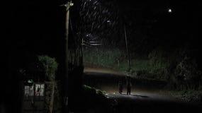 Tillbaka sikt av den bärande korgen för afrikansk man med kläder, två pojkar som går nära man till och med vägen på natten i regn arkivfoton
