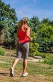 Tillbaka sikt av den blonda kvinnan för 20-tal som joggar med hörlurar Royaltyfria Foton