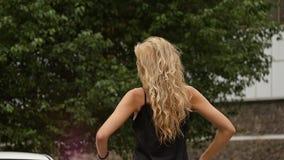 Tillbaka sikt av den blonda kvinnan på naturbakgrund Den härliga flickan poserar med flyghår långsam rörelse stock video