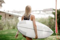 Tillbaka sikt av den blonda sexiga kvinnan i svartvit baddräktställning fotografering för bildbyråer