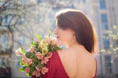Tillbaka sikt av den fantastiska och härliga unga kvinnan som utomhus rymmer en stor bukett av färgrika blommor nära byggnaderna  arkivbilder
