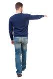 Tillbaka sikt av den gående stiliga mannen, i att peka för jeans Royaltyfri Bild