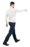 Tillbaka sikt av den gående stiliga mannen, i att peka för jeans Royaltyfria Bilder