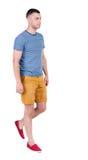 Tillbaka sikt av den gående stiliga mannen i kortslutningar gå ung grabb Royaltyfri Foto