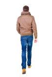 Tillbaka sikt av den gående stiliga mannen i jeans och omslag Fotografering för Bildbyråer