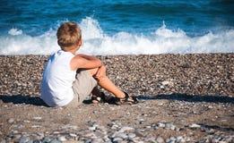Tillbaka sikt av den gulliga pojken på sjösidan. Arkivfoto
