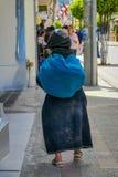 Tillbaka sikt av den infödda kvinnan som går i sthetrottoar i staden av Otavalo royaltyfria bilder