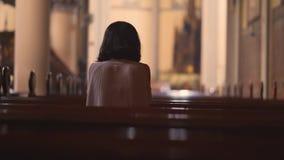 Tillbaka sikt av den kristna kvinnan som ber i kyrka stock video