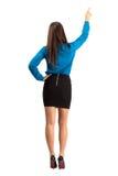 Tillbaka sikt av den långa kvinnan för hårbrunettaffär som pekar med blyertspennan arkivfoto