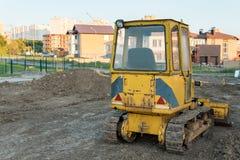 Tillbaka sikt av den lilla gula bulldozern på bakgrunden av nya privata hus, Royaltyfria Foton