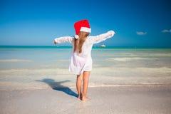 Tillbaka sikt av den lilla gulliga flickan i den röda hatten santa Royaltyfri Bild