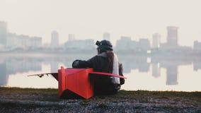 Tillbaka sikt av den lilla pilot- flickan som sitter med den roliga röda pappnivån på fantastisk fridsam ultrarapid för stadssjöp lager videofilmer
