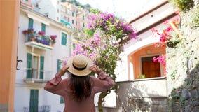 Tillbaka sikt av den lyckliga flickan som har gyckel under ferier i Cinque Terre Ung caucasian turist som går på den gamla gatan arkivfilmer