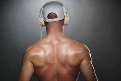 Tillbaka sikt av den muskulösa mannen med locket och hörlurar Arkivfoton