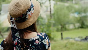 Tillbaka sikt av den nätta brunetten i sommarhatt på bygdbakgrund lager videofilmer