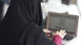 Tillbaka sikt av den oigenkännliga muslimkvinnan i svart hijab som arbetar på den moderna bärbara datorn i kafé Studera eller arb stock video