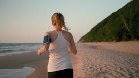 Tillbaka sikt av den rinnande kvinnan som joggar på stranden på havskusten på solnedgången med telefonen lager videofilmer