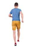 Tillbaka sikt av den rinnande mannen i t-skjorta och kortslutningar Arkivfoto