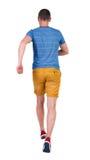 Tillbaka sikt av den rinnande mannen i t-skjorta och kortslutningar Royaltyfri Fotografi