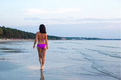 Tillbaka sikt av den sexiga kvinnan som går i vatten på stranden Royaltyfri Fotografi