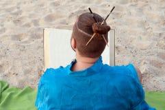 Tillbaka sikt av den skäggiga mannen med bullen och pinnar på huvudet i blått kimonosammanträde som rymmer boken royaltyfri fotografi