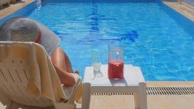 Tillbaka sikt av den slanka avslappnande near simbassängen för ung kvinna arkivfilmer
