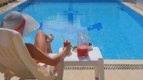 Tillbaka sikt av den slanka avslappnande near simbassängen för ung kvinna stock video
