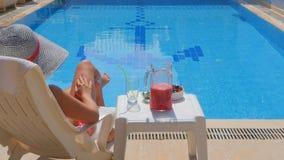 Tillbaka sikt av den slanka avslappnande near simbassängen för ung kvinna lager videofilmer