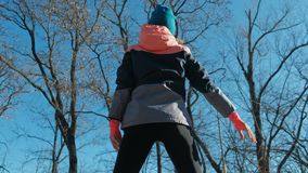 Tillbaka sikt av den slanka konditionkvinnan som utomhus utarbetar i solig vinter arkivfilmer