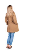 Tillbaka sikt av den stående unga härliga blonda kvinnan i bruna clo Arkivfoton