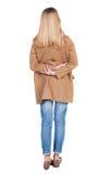 Tillbaka sikt av den stående unga härliga blonda kvinnan i bruna clo Fotografering för Bildbyråer