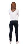 Tillbaka sikt av den stående unga härliga blonda kvinnan i jeans Royaltyfri Fotografi