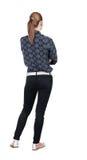 Tillbaka sikt av den stående unga härliga blonda kvinnan i jeans Royaltyfria Foton
