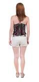 Tillbaka sikt av den stående unga härliga blonda kvinnan i kortslutningar Royaltyfria Bilder