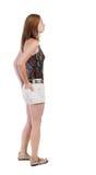 Tillbaka sikt av den stående unga härliga blonda kvinnan i kortslutningar Arkivbild