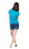 Tillbaka sikt av den stående unga härliga brunettkvinnan i kortslutningar Arkivbild