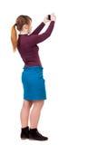 Tillbaka sikt av den stående unga härliga kvinnan och att använda en mobil arkivbild