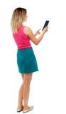 Tillbaka sikt av den stående unga härliga kvinnan som använder en mobil phon Royaltyfri Bild