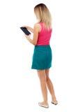 Tillbaka sikt av den stående unga härliga kvinnan som använder en mobil phon Arkivbilder