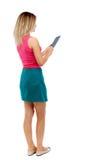 Tillbaka sikt av den stående unga härliga kvinnan som använder en mobil phon Arkivbild