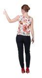 Tillbaka sikt av den stående unga tummen för visning för rödhårig manaffärskvinna Arkivbilder